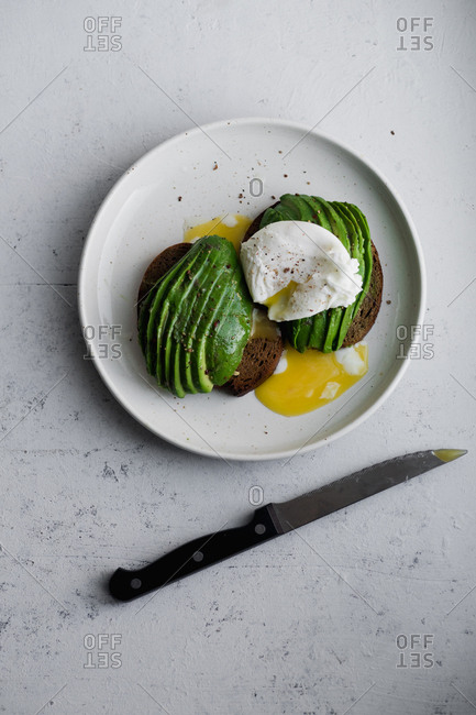 Avocado sandwich on rye toasted bread with poached egg and knife