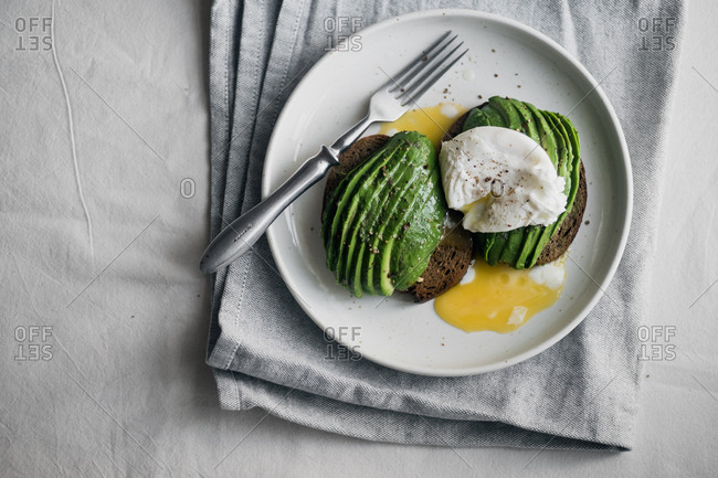 Avocado sandwich on rye toasted bread with poached egg and fork