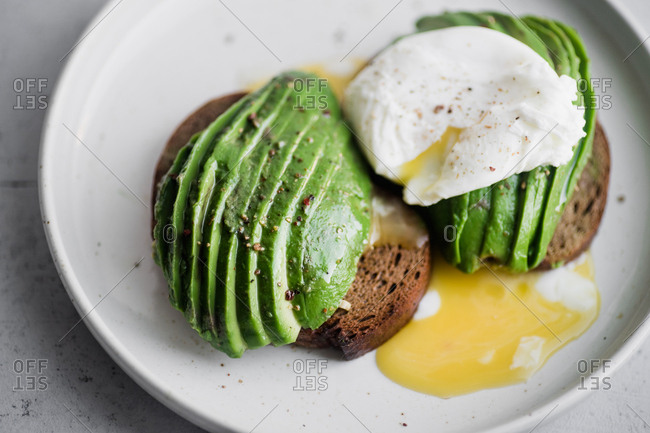 Close up of avocado sandwich on rye toasted bread with poached egg