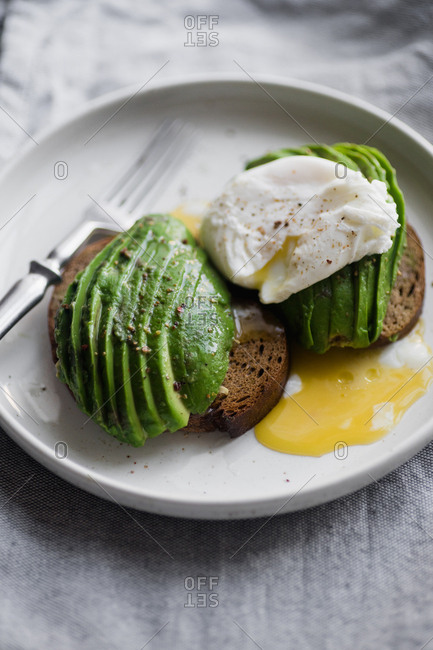 Close up of avocado sandwich on rye toasted bread with poached egg and fork