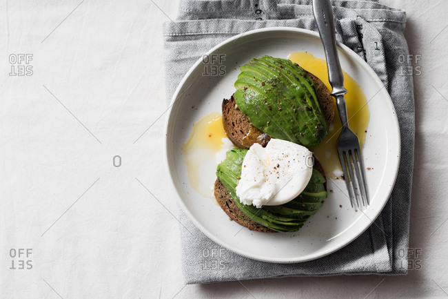 Top view of avocado sandwich on rye toasted bread with poached egg and fork