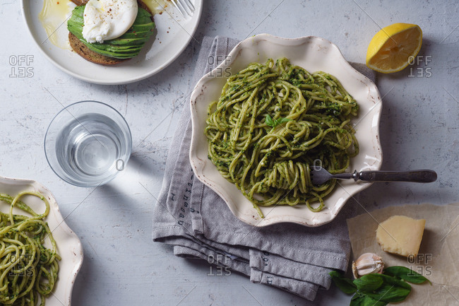 Overhead view of healthy dinner with basil pesto spaghetti and avocado toasts with poached egg