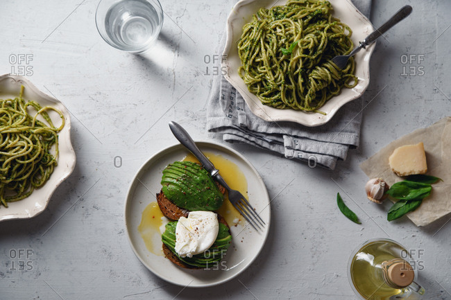 Top view image of healthy dinner with basil pesto spaghetti and avocado toasts with poached egg