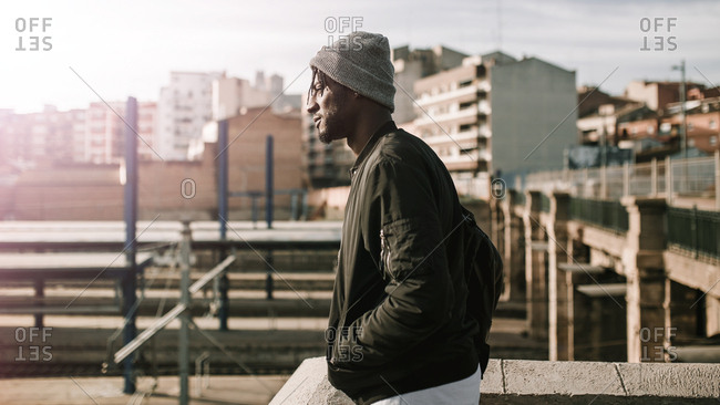 Side view of young african american man observing city