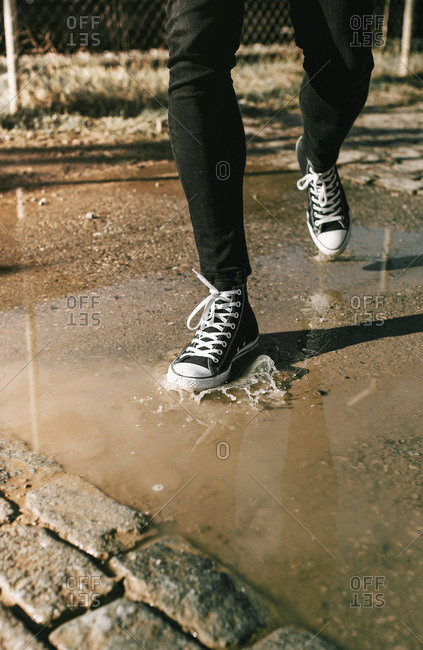 Detail of feet walking and splashing by the puddle