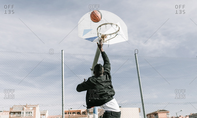 Rear view of young african man throwing a ball in a basket on a basketball court