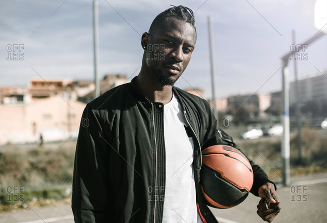 Front view of young african man with black jacket looking at camera holding a basket ball
