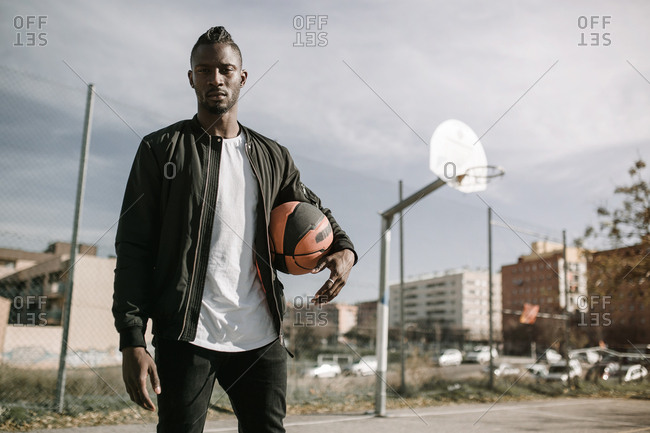 Front view of young african man with black jacket looking at camera holding a basket ball in a court