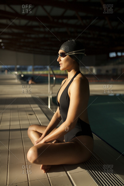 Young beautiful woman sitting on the edge of the indoor pool with black swimsuit