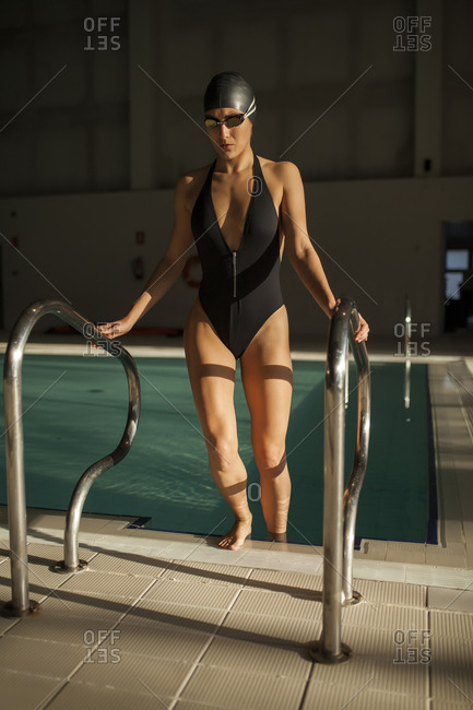 Young beautiful woman leaves the indoor pool by the stairs with black swimsuit, front view