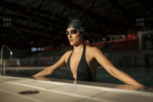 Young beautiful woman on the curb of the indoor pool, wearing black swimsuit