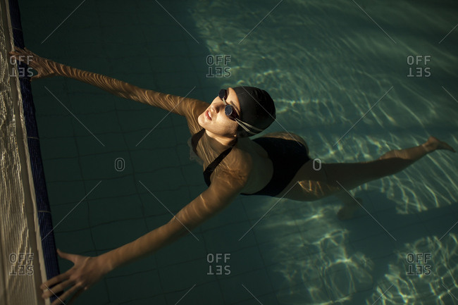 Young beautiful woman on the curb of the indoor pool, wearing black bathing suit, floating in the water