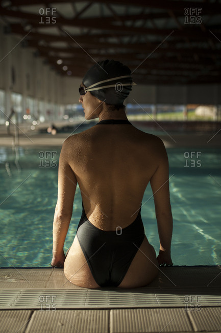 Young beautiful woman on the curb of the indoor pool, with black swimsuit, back view