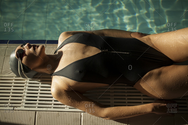 Young beautiful woman lying on the curb of the indoor pool, wearing black swimsuit