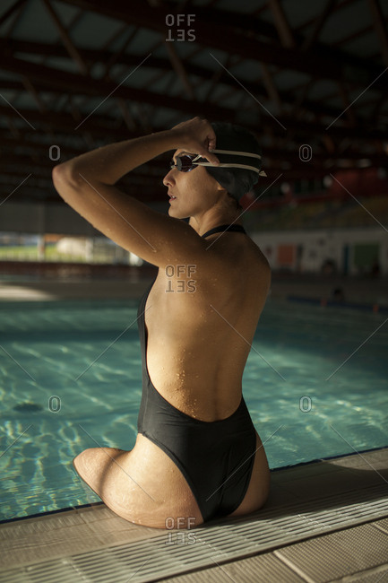 Young beautiful woman on the curb of the indoor pool, wearing black swimsuit, puts on the swimming goggles, side view