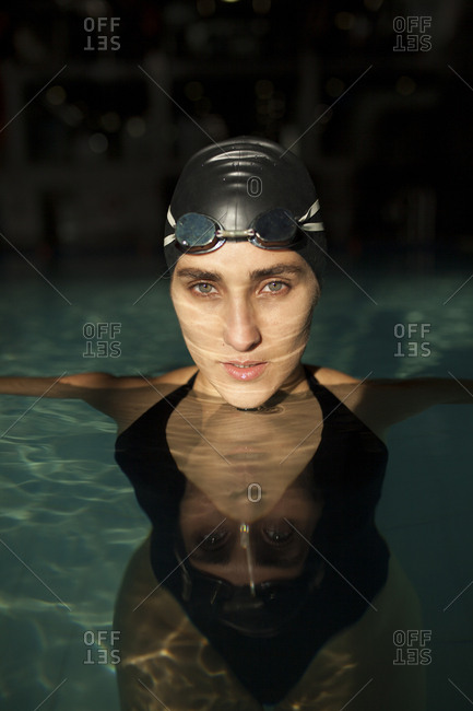 Young beautiful woman in the indoor pool, wearing black swimsuit, look at camera
