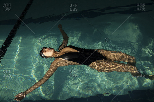 Young beautiful woman inside the indoor pool, wearing black swimsuit, floating on her back