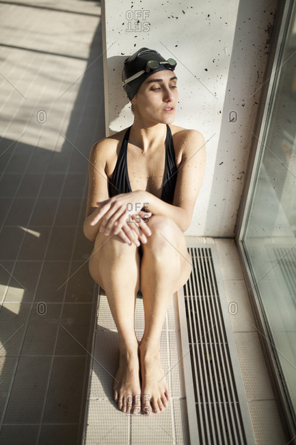 Portrait of beautiful young swimmer woman sit down with black swimwear hat and swimming goggles