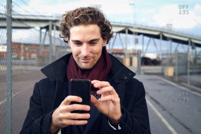 Attractive middle-aged man using cell phone outdoors