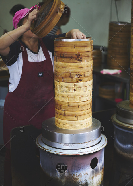 Taiwan, China - October 29, 2017: A lady lifting the lid of a stack of Asian steamer pots to see if dumplings are ready