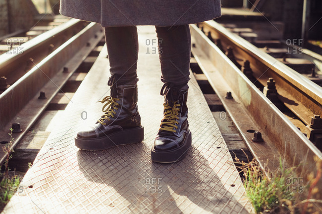 Close up of person wearing platform boots standing in the middle of railroad tracks