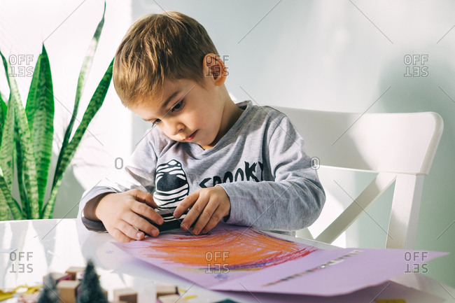 Boy making colorful design on a card