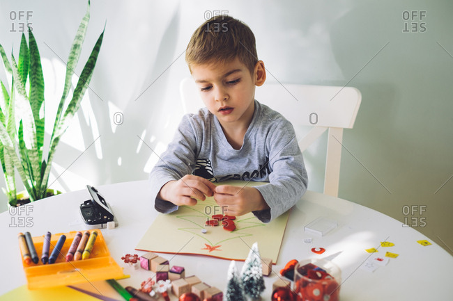 Boy decorating a Christmas craft with cutouts