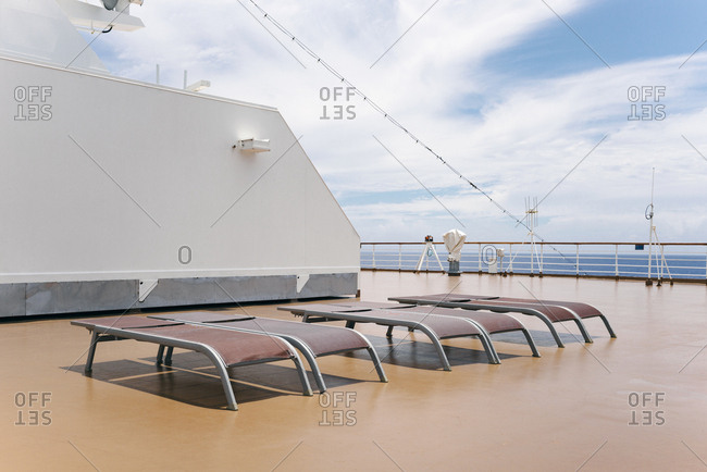 Empty lounge chairs on the deck of a cruise ship