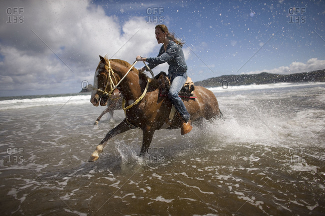 Young woman horseback riding at a beach.