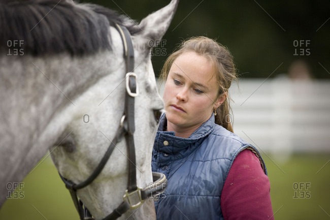 Young woman looking at her grey horse while standing in a paddock.