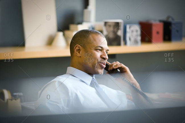 Mid-adult businessman talking on a telephone inside his office.