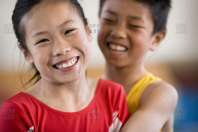 Portrait of a girl being hugged by a boy in a gym.