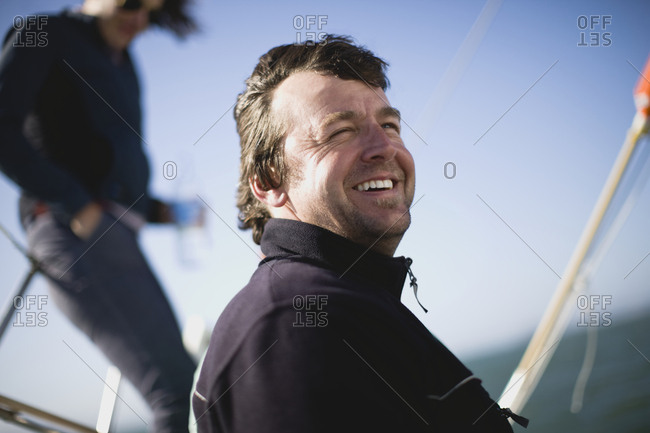 Mid-adult man sitting on a sail boat at sea.
