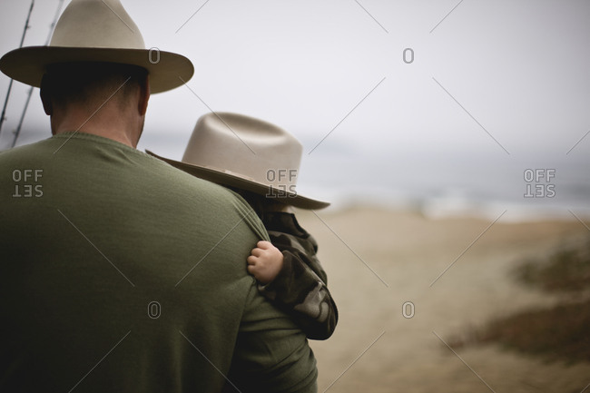 Father holding his young son on a beach while both wearing hats.