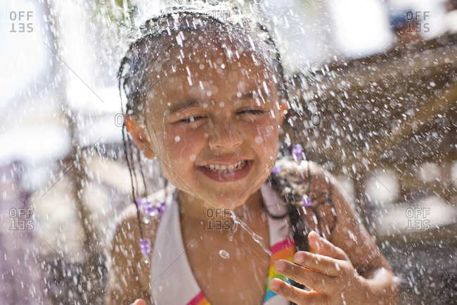Smiling young girl standing under an outdoor shower.