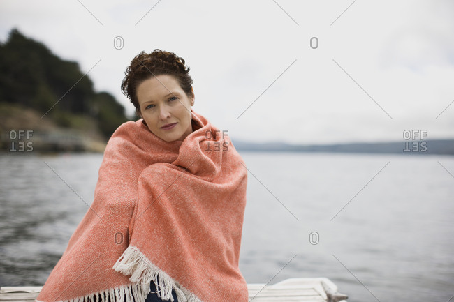 Portrait of a mid-adult woman wrapped in a woolen blanket by the sea.