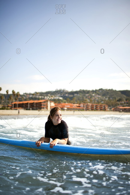 Young woman heading into the surf with a surfboard.
