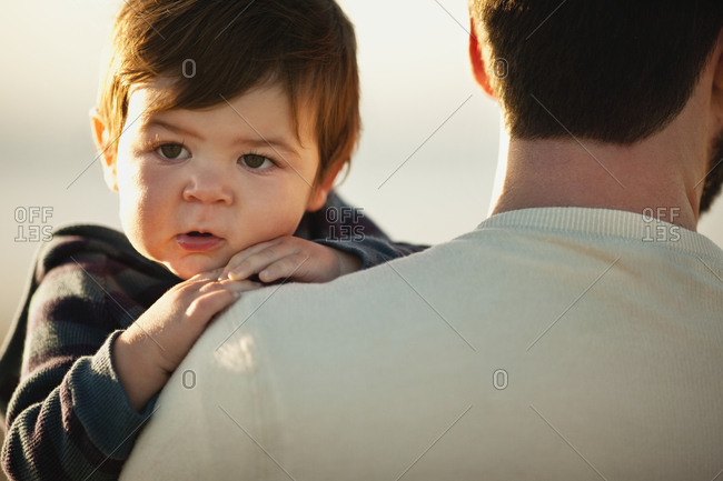 Baby boy looks over his father's shoulder.