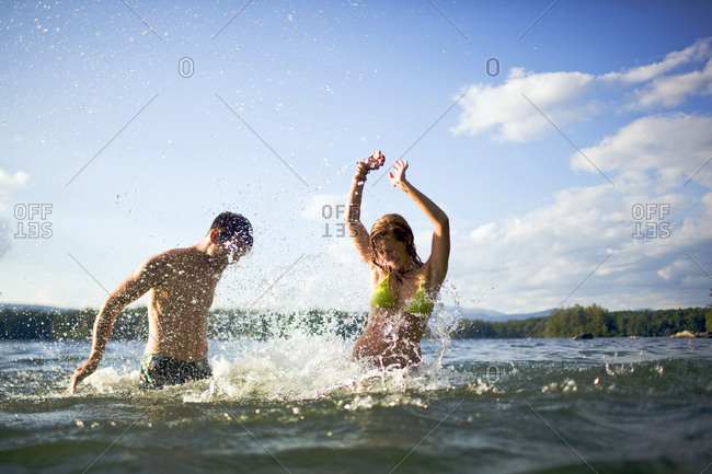 Young couple splashing in a lake.