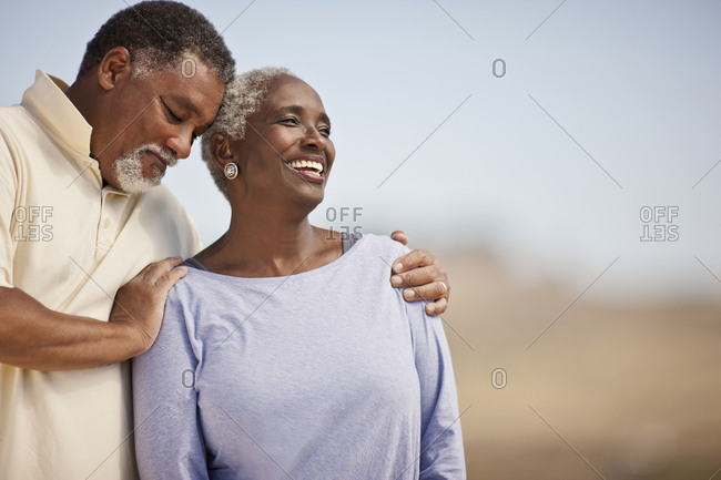 Smiling mature couple standing on a beach.