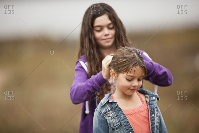 Older girl braids a younger girl's hair as they stand outside.