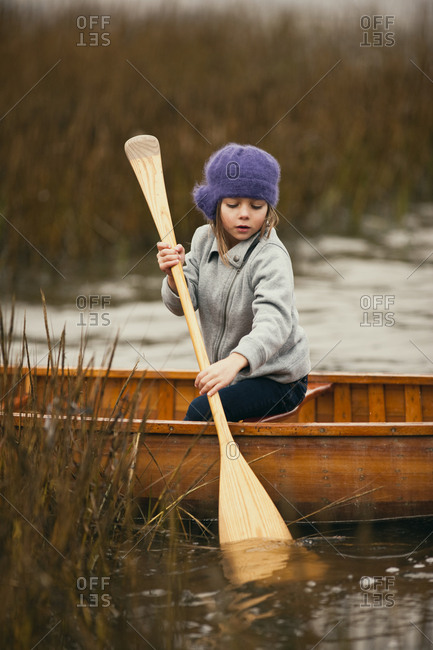Young girl looks down as she tries to paddle a wooden canoe through reeds in a lake.