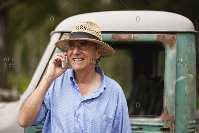 Mature man talking on cell phone while leaning on truck.