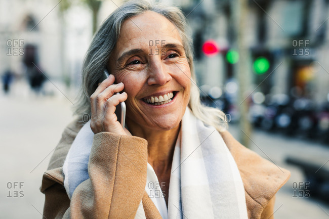 Smiling senior woman using her phone on the street in winter.