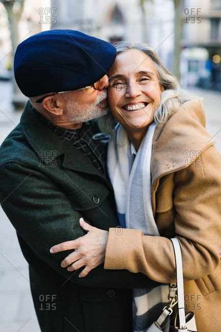 Happy senior couple embracing together on the street in winter.