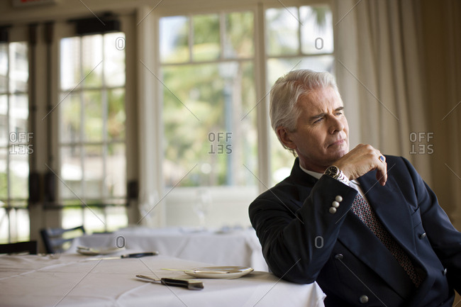 Businessman sits in restaurant looking into space in thought.