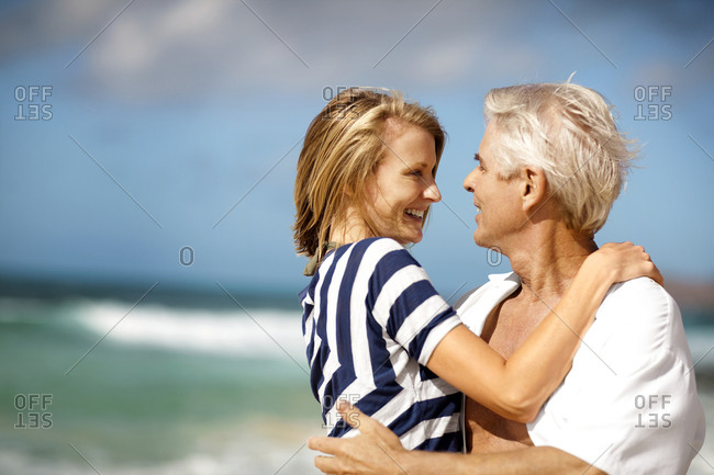 Smiling couple smiling at each other while hugging at the beach.