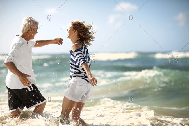 Laughing couple playing in the surf at a beach.