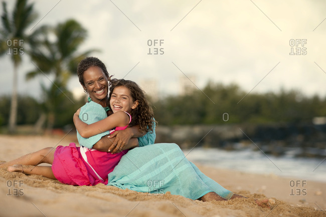 Smiling mature woman sitting with her granddaughter on a sandy beach.