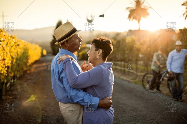 Senior couple dancing in the vineyard.